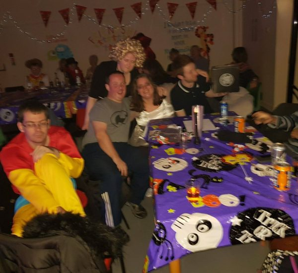 Young adult service users sitting and posing for a photo at the COJAC Halloween party